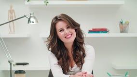 Una giovane donna che si siede e che sorride in un ufficio fotografie stock