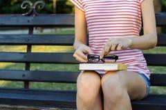Una giovane donna che si siede nel parco e che tiene un libro con i vetri Immagine Stock Libera da Diritti