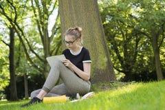 Una giovane donna che si siede sotto un albero e sta scrivendo in una cartella fotografie stock