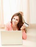 Una giovane donna che si trova sul pavimento con un computer portatile fotografia stock libera da diritti