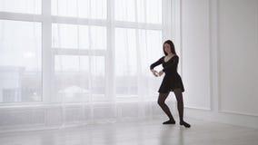 Una giovane donna che somiglia ad una ginnasta sta in una posizione di balletto archivi video