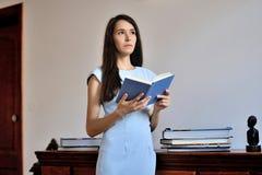 Una giovane donna che sta con un libro aperto in sue mani Immagini Stock Libere da Diritti