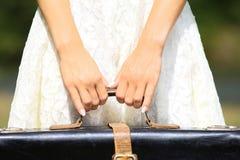 Una giovane donna che tiene una valigia Fotografie Stock Libere da Diritti