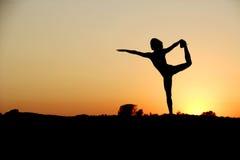 Una giovane donna in cima ad una roccia che fa yoga Fotografia Stock
