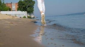 Una giovane donna con una figura fine è impegnata in ginnastica nel mare all'alba Funziona lungo il litorale in cuffie archivi video