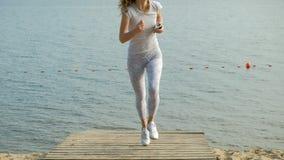 Una giovane donna con una figura fine è impegnata in ginnastica nel mare all'alba Funziona lungo il litorale in cuffie stock footage