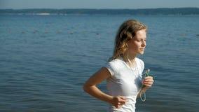 Una giovane donna con una figura fine è impegnata in ginnastica nel mare all'alba Funziona lungo il litorale in cuffie video d archivio