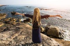 Una giovane donna con i dreadlocks biondi che stanno sulla riva rocciosa dell'oceano verso il sole Fotografie Stock