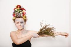 Una giovane donna con i fiori lei capa e sulle mani Immagine della primavera con i fiori Uomo con una pianta variopinta La ragazz Fotografie Stock Libere da Diritti