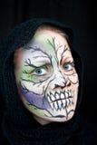 Una giovane donna con la pittura del fronte di Halloween Immagini Stock