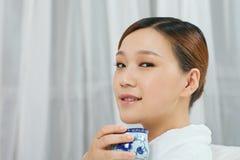 Una giovane donna con un accappatoio che gode del tè Fotografia Stock Libera da Diritti