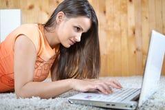 Una giovane donna con un computer portatile Immagini Stock Libere da Diritti