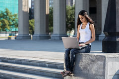 Una giovane donna con un computer portatile che si siede sulle scale, vicino al univ Immagini Stock