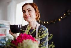 Una giovane donna creativa in un negozio di fiore Una partenza dell'affare del fiorista fotografia stock