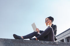 Una giovane donna d'avanguardia dei pantaloni a vita bassa sta ridendo esaminando la sua nuova compressa elettronica all'aperto Fotografia Stock Libera da Diritti