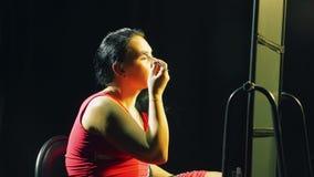 Una giovane donna davanti ad uno specchio mette gli ombretti luminosi sulle sue palpebre con una spazzola stock footage