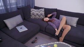 Una giovane donna decolla le sue scarpe a tacco alto e si riposa sul sofà archivi video