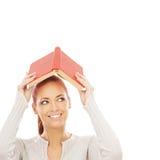 Una giovane donna della testarossa che tiene un libro rosso Immagini Stock