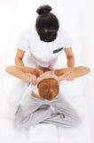 Una giovane donna della testarossa su un massaggio tailandese Immagini Stock