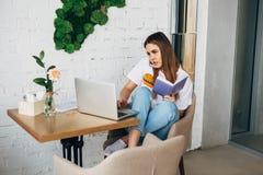Una giovane donna delle free lance con un taccuino e un computer portatile lavora in un caffè Immagine Stock Libera da Diritti