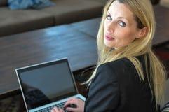 Una giovane donna di affari che usando una cima del rivestimento Fotografie Stock Libere da Diritti