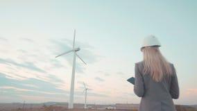 Una giovane donna di affari in un casco si trova sul cantiere contro il mulino a vento Affare di costruzione per i giovani E archivi video