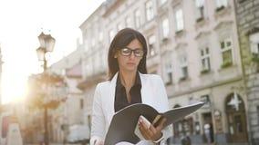 Una giovane donna di affari va alla città ed esamina i documenti archivi video