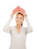 Una giovane donna di redhead che tiene un libro rosso Fotografia Stock