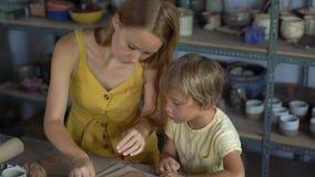 Una giovane donna ed il suo poco figlio su una classe matrice delle terraglie stock footage