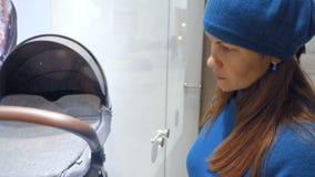 Una giovane donna esamina una finestra del negozio con una carrozzina video d archivio