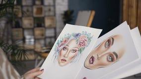 Una giovane donna esamina gli schizzi della progettazione il salone di bellezza Buon lavoro del modo dei giovani di Beautiful del stock footage