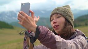 Una giovane donna fa il selfie sulle montagne Una ragazza turistica del asain abbastanza adorabile prende una foto del selfie usa archivi video