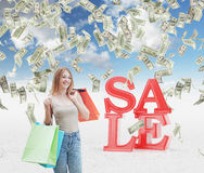 Una giovane donna felice con i sacchetti della spesa colourful dai negozi operati Le note del dollaro stanno cadendo dal cielo co Fotografia Stock