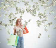 Una giovane donna felice con i sacchetti della spesa colourful dai negozi operati Le note del dollaro stanno cadendo dal soffitto Fotografia Stock Libera da Diritti