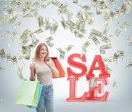 Una giovane donna felice con i sacchetti della spesa colourful dai negozi operati Le note del dollaro stanno cadendo dal soffitto Fotografie Stock