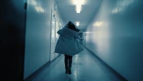 Una giovane donna funziona a partire dal suo inseguitore lungo un corridoio scuro stock footage