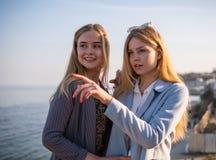 Una giovane donna gemellata di due adolescenti che laughting e che si diverte vicino al mare al tempo di tramonto immagini stock libere da diritti
