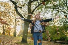 Una giovane donna getta le foglie in un parco fotografia stock