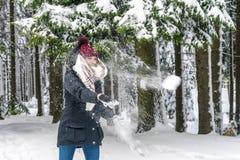 Una giovane donna getta una palla di neve immagine stock libera da diritti