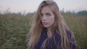 Una giovane donna gira l'esame dei sorrisi della macchina fotografica e gira via stock footage