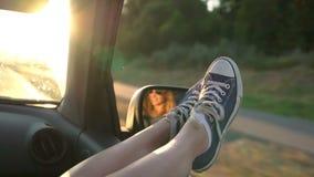Una giovane donna gode di di viaggiare in un'automobile attaccando fuori le sue gambe in una finestra aperta archivi video