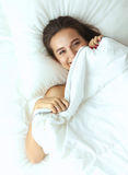 Una giovane donna graziosa che dà una occhiata da sotto le coperture Fotografie Stock