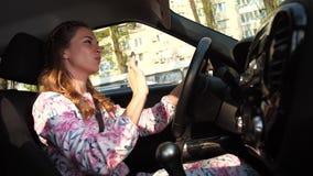 Una giovane donna guida attraverso la città, ascolta musica, canta e balla dietro la ruota 4K Mo lento video d archivio
