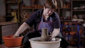 Una giovane donna impara creare i prodotti dell'argilla, gli impianti dello studente con una ruota del ` s del vasaio ed il mater stock footage
