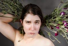 Una giovane donna incredula con i fiori Fotografie Stock Libere da Diritti