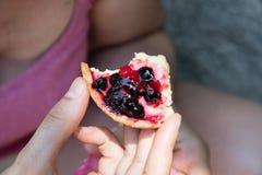 Una giovane donna mangia un dolce con frutta fotografia stock libera da diritti
