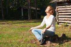 Una giovane donna medita su natura Fotografia Stock