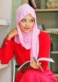 Una giovane donna musulmana che legge un libro Immagine Stock Libera da Diritti