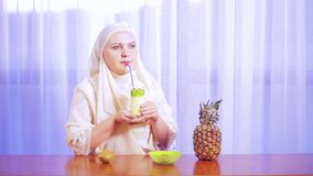 Una giovane donna musulmana in una sciarpa leggera beve il frullato della frutta da una paglia video d archivio