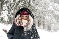 Una giovane donna nel legno mentre sta nevicando fotografie stock